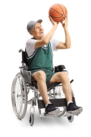 Senior disabled man in wheelchair shooting a basketball solated on white background