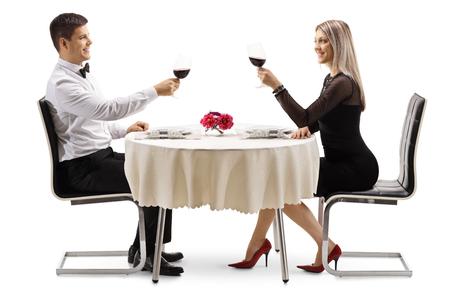 Giovane coppia elegante che brinda con il vino a un tavolo isolato su sfondo bianco