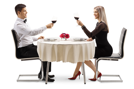 Young elegant couple toasting with wine at a table isolated on white background
