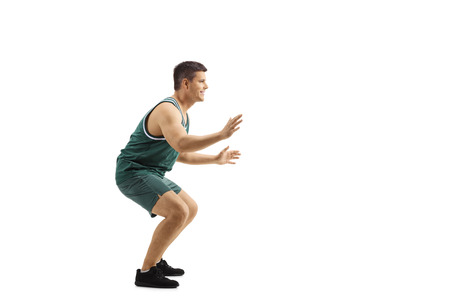 Full length profile shot of a man playing defence in basketball isolated on white background