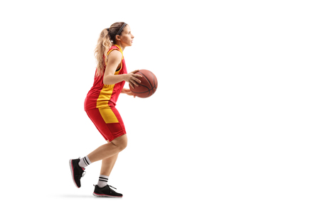Full length shot of a female basketball player running with a ball isolated on white background