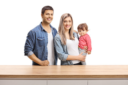 Young family of a mother, father and a baby girl posing behind a wooden counter isolated on white background