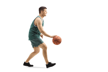 Full length profile shot of a guy playing basketball and leading a ball isolated on white background Stok Fotoğraf
