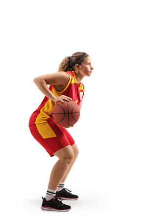 Full length profile shot of a female basketball player passing a ball isolated on white background