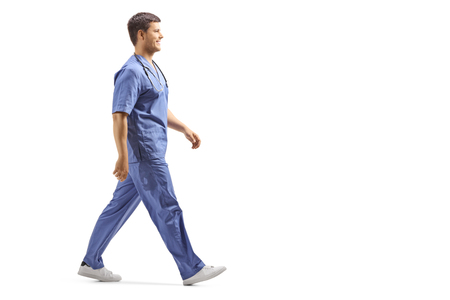 Full length profile shot of a young male doctor in a blue uniform walking isolated on white background