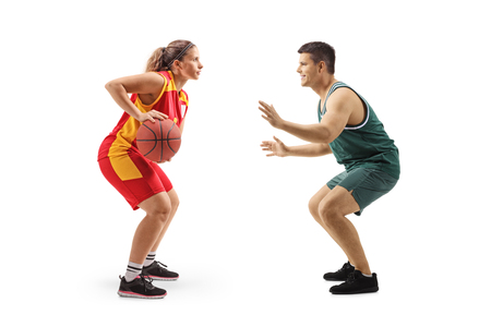 Full length profile shot of a female basketball player playing with a male basketball palyer isolated on white background