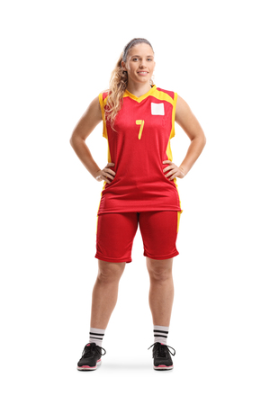 Full length portrait of a female basketball player posing and smiling at the camera isolated on white background