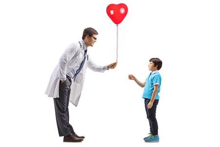 Full length profile shot of a male doctor giving a red heart balloon to a little boy isolated on white background