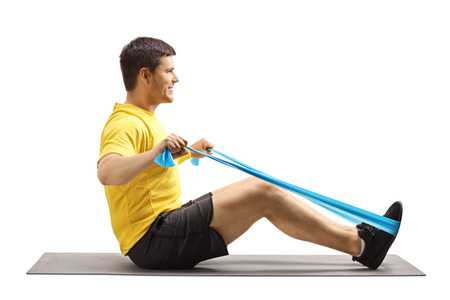 Hombre guapo joven sentado en una colchoneta y hacer ejercicio con una banda de goma elástica aislada sobre fondo blanco Foto de archivo