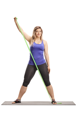 Full length portrait of a young healthy woman exercisingon a mat with a stretching rubber band isolated on white background