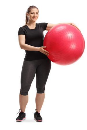 Full length portrait of a young smiling woman posing with a fitness ball isolated on white background