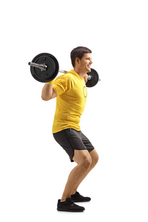 Full length shot of a young man lifting weights and kneeling isolated on white background