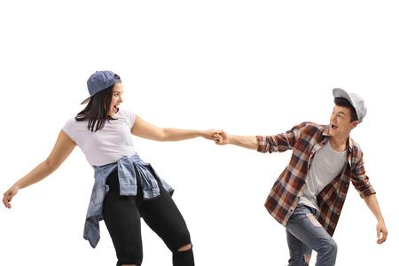 Happy teenage boy pulling a teenage girl isolated on white background 版權商用圖片