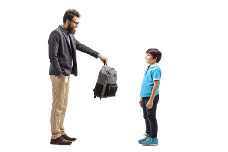 Full length shot of a father giving a backpack to his son isolated on white background
