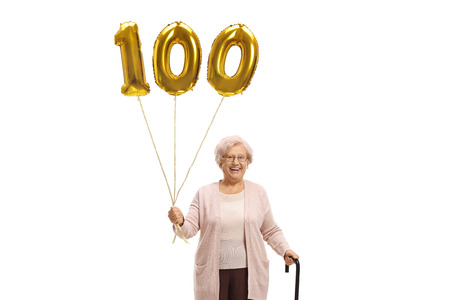 Old woman with a golden number hundred balloon and a walking cane isolated on white
