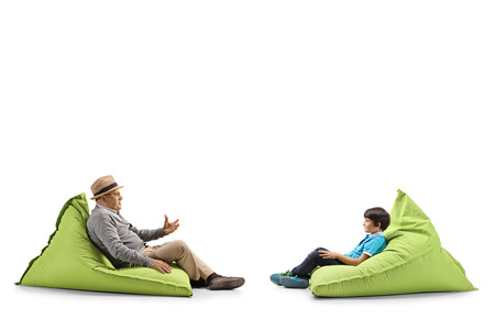 Full length profile shot of a grandfather and grandson sitting on bean bags and talking isolated on white Stok Fotoğraf