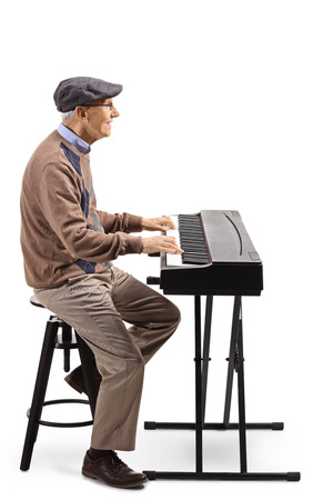 Full length profile shot of an elderly man playing a digital piano isolated on white