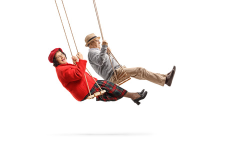 Full length shot of a senior husband and wife looking at the camera and swinging on swings isolated on white