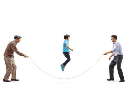 Disparo de longitud completa de un niño saltando una cuerda sostenida por su padre y su abuelo aislado sobre fondo blanco.