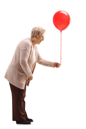 Full length profile shot of a senior woman holding a red balloon isolated on white background