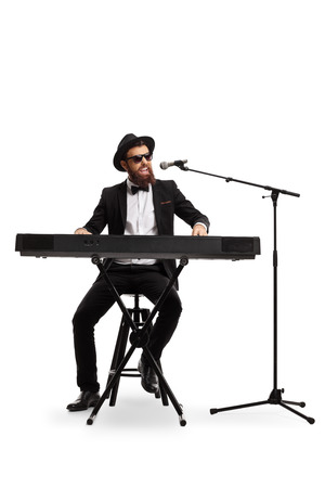 Full length portrait of a male musician playing a digital piano and singing on a microphone isolated on white background