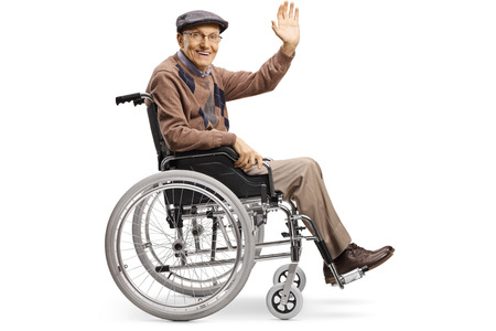 Full length shot of a senior disabled man waving from a wheelchair isolated on white background
