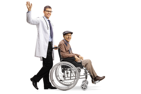 Full length shot of a young male doctor waving and pushing an elderly male patient in a wheelchair isolated on white background
