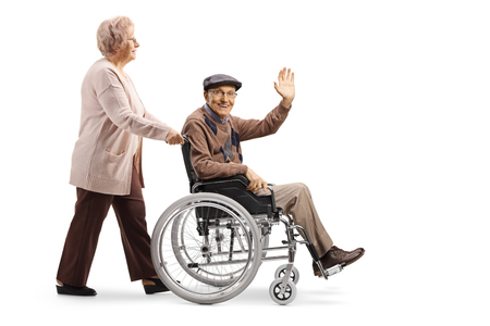 Full length shot of an elderly woman pushing an elderly man waving and sitting in a wheelchair isolated on white background