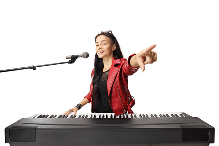 Young female musician playing a digital piano, singing on a microphone and pointing isolated on white background