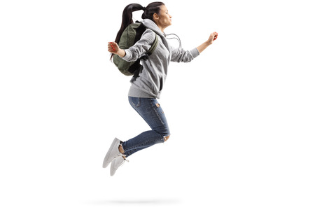 Full length profile shot of a young female student jumping isolated on white background