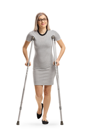 Full length portrait of a young woman with an injured leg walking with crutches isolated on white background 版權商用圖片