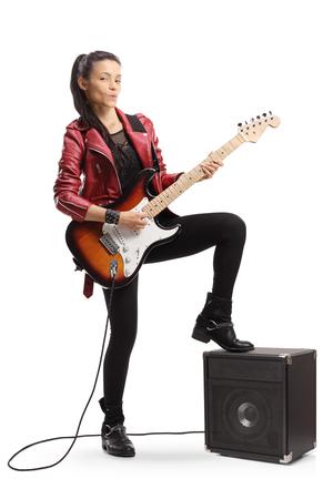Retrato de cuerpo entero de una joven guitarrista de pie junto a un amplificador aislado sobre fondo blanco.