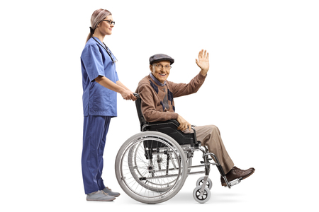 Full length profile shot of a female nurse pushing a senior patient sitting in a wheelchair and greeting with hand isolated on white background