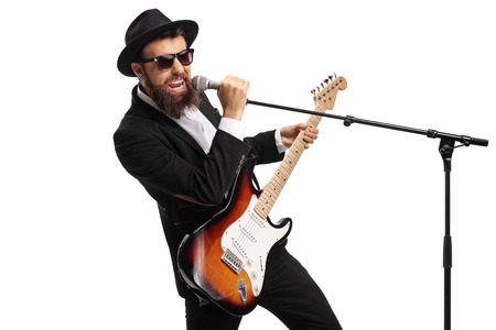 Portrait of a male singer with a bass guitar holding a microphone isolated on white background Stock Photo