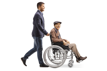 Full length shot of a young man pushing an elderly man in a wheelchair isolated on white background