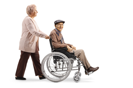 Full length shot of an elderly woman pushing an elderly man in a wheelchair isolated on white background