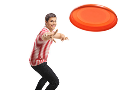 Young handsome guy throwing a frisbee isolated on white background