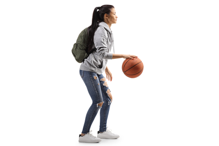 Full length profile shot of a female student with a basketball isolated on white background