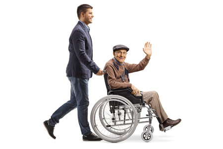 Full length shot of a son pushing his father waving from a wheelchair isolated on white background