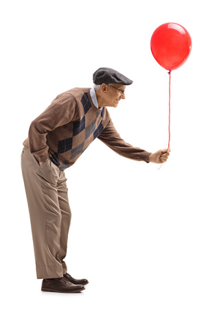 Full length profile shot of a senior man handing a red balloon isolated on white background