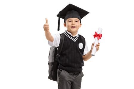 Schoolboy in a uniform with graduation hat and diploma making thumb up gesture isolated on white background