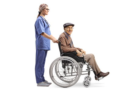 Full length profile shot of a female nurse pushing a senior man sitting in a wheelchair isolated on white background
