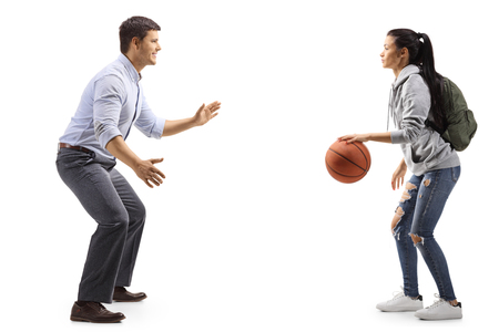 Full length shot of a man and a female student playing basketball isolated on white background Stock Photo