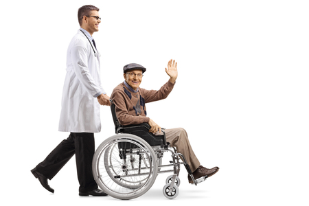 Full length shot of a young male doctor pushing a senior man sitting in a wheelchair and waving isolated on white background Stock Photo