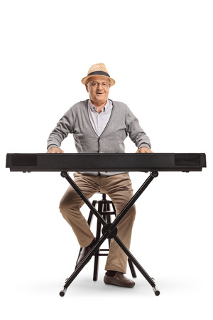 Full length portrait of a senior man sitting and playing a keyboard isolated on white background