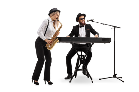 Full length shot of a young woman playing a sax and a man playing keyboards isolated on white background