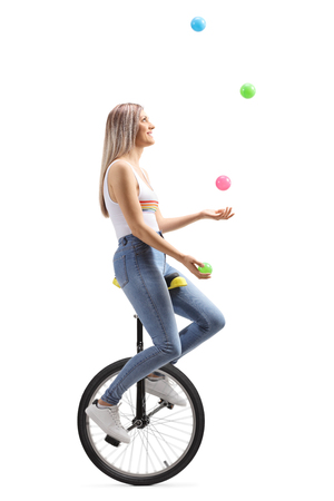 Full length profile shot of a young woman juggling with balls on a unicycle isolated on white background