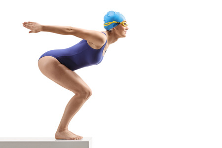 Full length profile shot of a woman in a swimming suit and cap preparing to jump isolated on white background