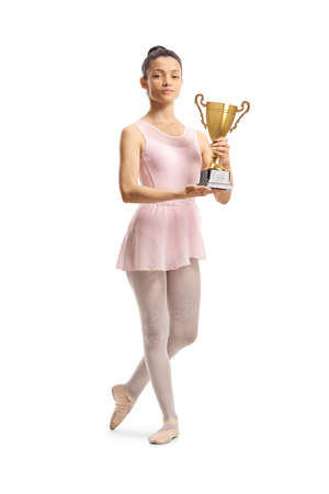 Full length portrait of a young ballerina posing with a gold trophy cup isolated on white background