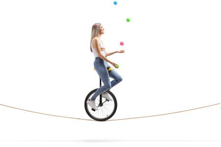 Profil de toute la longueur d'une jeune femme chevauchant un monocycle sur une corde et jonglant avec des balles isolées sur fond blanc Banque d'images